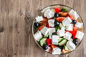 foto of greek  - Greek salad in bowl on wooden table with copy space - JPG