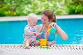 stock photo of shovel  - Happy family young active mother and adorable curly little baby having fun in a swimming pool playing with toy watering can and shovel enjoying summer vacation at a tropical resort - JPG