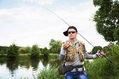 image of sun perch  - Young man is fishing on the bank of the river - JPG