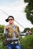 stock photo of sun perch  - Young man is fishing on the bank of the river - JPG