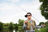 stock photo of sun perch  - Young man is fishing on the bank of the river.Fisherman caught perch and holds it in his hand. ** Note: Soft Focus at 100%, best at smaller sizes - JPG
