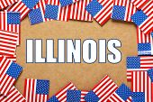 stock photo of illinois  - Miniature flags of the United States of America form a border on brown card around the name of the state of Illinois - JPG