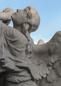 image of blue angels  - A statue of an supplicant angel carved in stone with a blue sky in the background - JPG