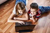 stock photo of fanny  - Children with laptop lying on the floor - JPG