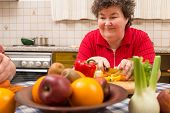 stock photo of physically handicapped  - a mentally disabled woman learns cooking in the kitchen - JPG
