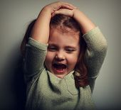 image of anger  - Anger shouting kid holding head with open mouth - JPG