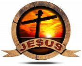 stock photo of cloudy  - Round wooden icon with cross silhouette at the sunset over the sea with cloudy sky wooden ribbon with text Jesus - JPG