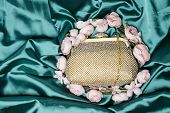 stock photo of clutch  - gold clutch in flowers on green silk - JPG