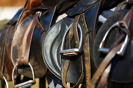 picture of western saddle  - A saddles laying on the rustic fence in warm sunlight - JPG