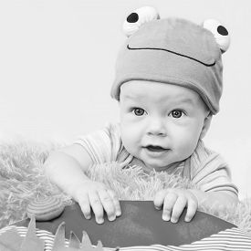 stock photo of baby frog  - cute baby playing in the hat frog lying on his stomach on a white background  - JPG