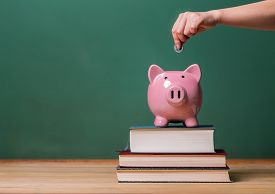 stock photo of chalkboard  - Person depositing money in a pink piggy bank on top of books with chalkboard in the background as concept image of the costs of education  - JPG