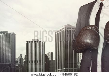 Businessman in boxing gloves on cityscape background