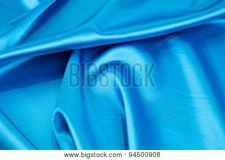 Folds of light blue silk cloth texture.
