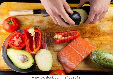 Chef Is Slicing Eggplant On A Wooden Board