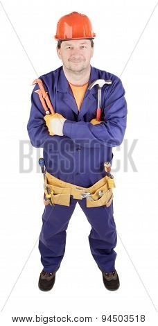 Worker in hard hat holding hammer and wrench.