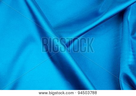 Cloth with folds of deep blue silk texture.