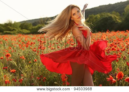 Sexy Blond Girl In Elegant Dress Posing In Summer Field Of Red Poppies