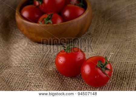 Couple Of Red Juicy Tomatoes In Front Of Bowl Full Of Others
