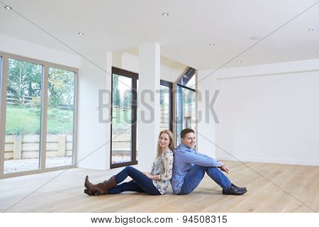 Happy Young Couple Sitting On Floor In New Home