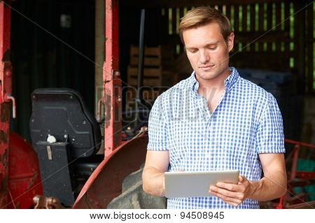Farmer With Old Fashioned Tractor Using Digital Tablet