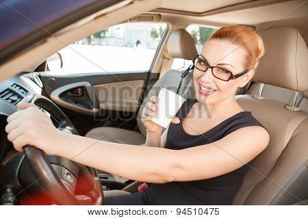 Smiling businesswoman in car with cup of coffee