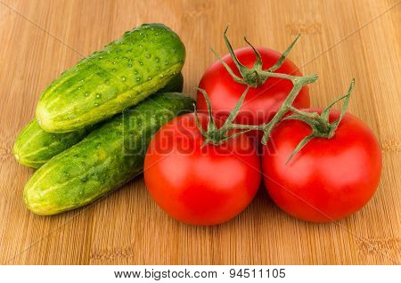 Ripe Red Tomatoes On Branch And Cucumber On Board