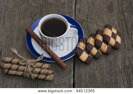 Cup Of Black Coffee And Two Rows Of Cookies On The Shabby Desktop