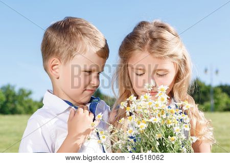 Pretty kids standing with bunch of flowers