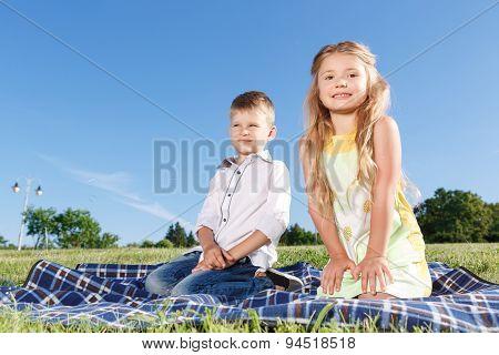 Joyful kids sitting on blanket