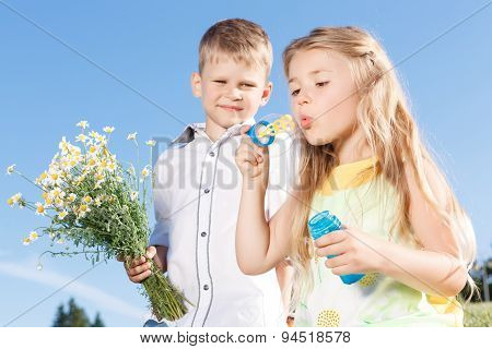 Positive children blowing soup bubbles