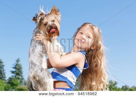 Smiling little girl holding dog