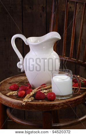Milk In A Transparent Mug And A Ripe Strawberry On A Wooden Table