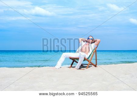 Young, fit, athletic and handsome man relaxing on a summer beach