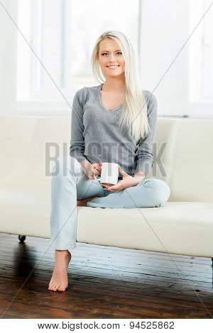 Beautiful girl relaxing on a white sofa at home and drinking tea