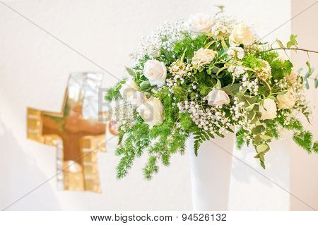 A bouquet of white flowers in front of the white altar with a golden cross