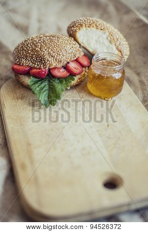 Breakfast Of Berries With A Bun And Honey On A Wooden Board