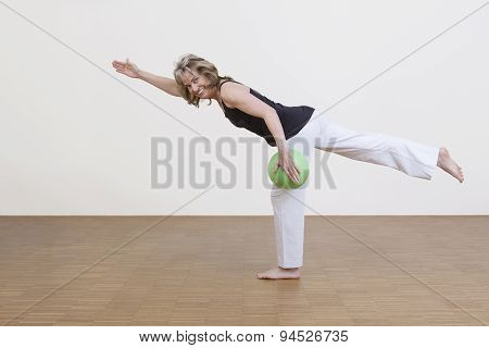 Woman Exercises With Green Ball