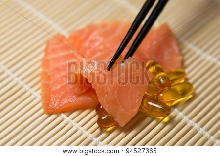 Salmon Sashimi Mixed With  Fish Oil Capsules With Chopstick Grab A Slice Of Salmon
