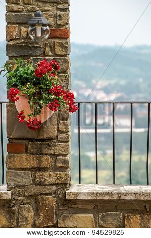 Flowers In A Pot On A Stone Wall Under The Lamp