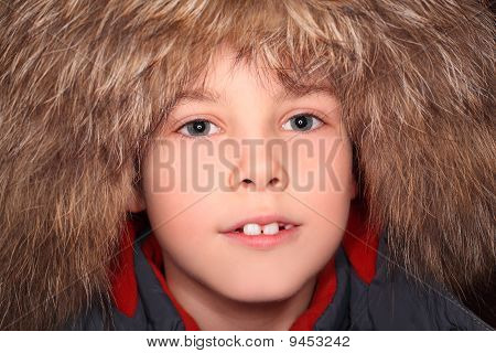 Portrait Of Little Boy In Big Fur Hood, Looking At Camera