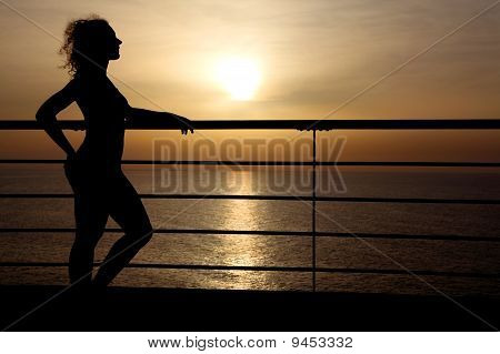 Silhouette Of Curl Girl Standing On Cruise Liner Deck, Hand On Rail, Side View, Sunset On Background