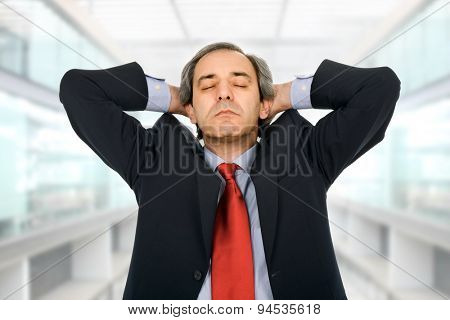 Businessman gestures with a headache at the office