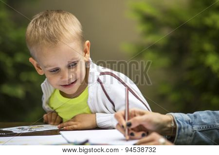 Little boy learning to draw with a pencil and with interest the hands of an adult.