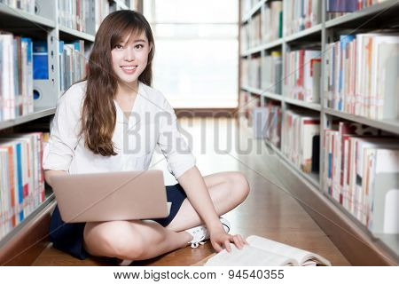 Asian beautiful female student studying in library with laptop