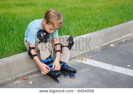 Boy with rollerblades sitting on edge of road.