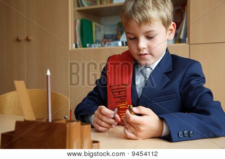 First class. Boy in school uniform at his desk pen in hand.