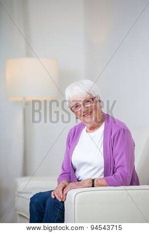 Portrait of a senior woman at home - Looking happy, looking at the camera, smiling while sitting on the sofa in her living room