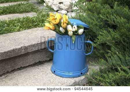 Blue enamel jug on stone steps