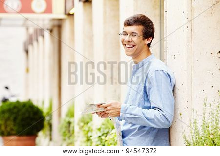 Young cheerful man in glasses and blue shirt leaning on stone wall holding map during vacation tour