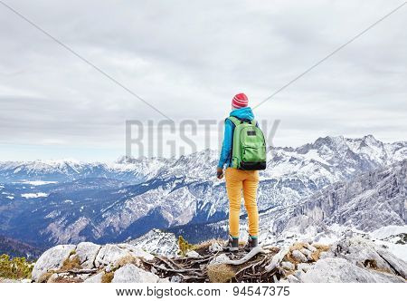 Female hiker with backpack standing on top of mountain